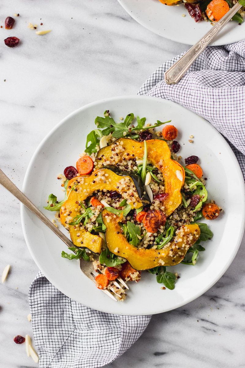 fall acorn squash salad with carrots and arugula in white plate with fork by fork in the kitchen