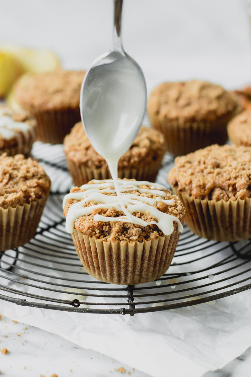 apple cider streusel muffins on cooling rack with drizzle by fork in the kitchen