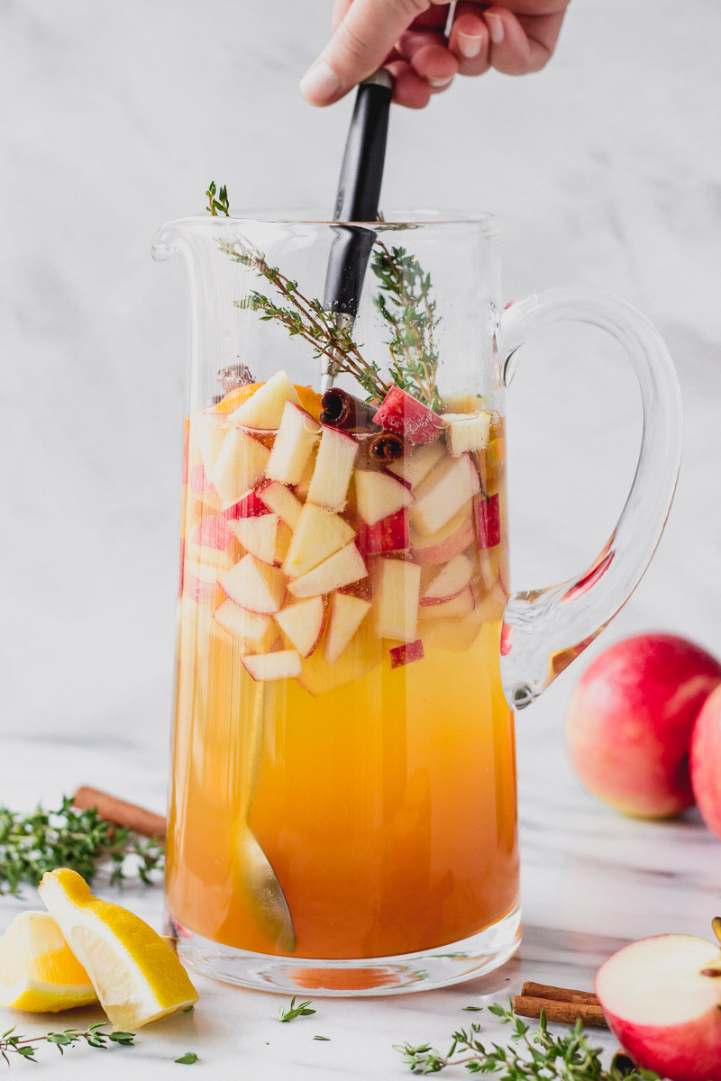 stirring apple cider sangria in pitcher with cinnamon, thyme, and apples by fork in the kitchen