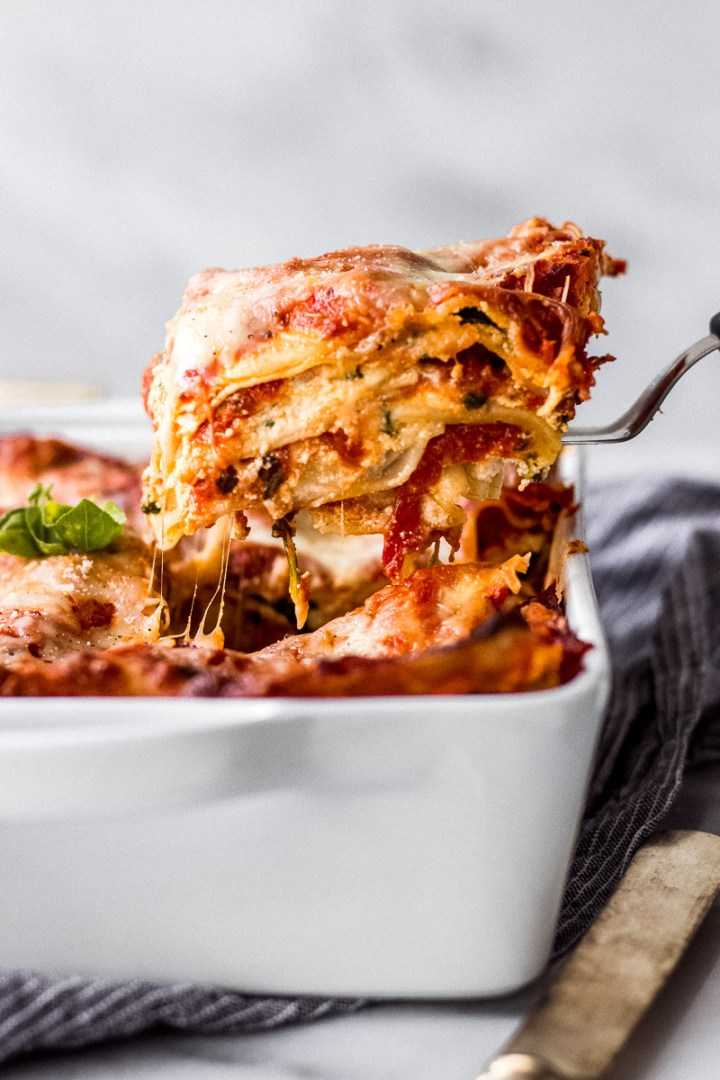 Vegetarian Spinach Ricotta Lasagna in white casserole dish with linen and knife by Fork in the Kitchen
