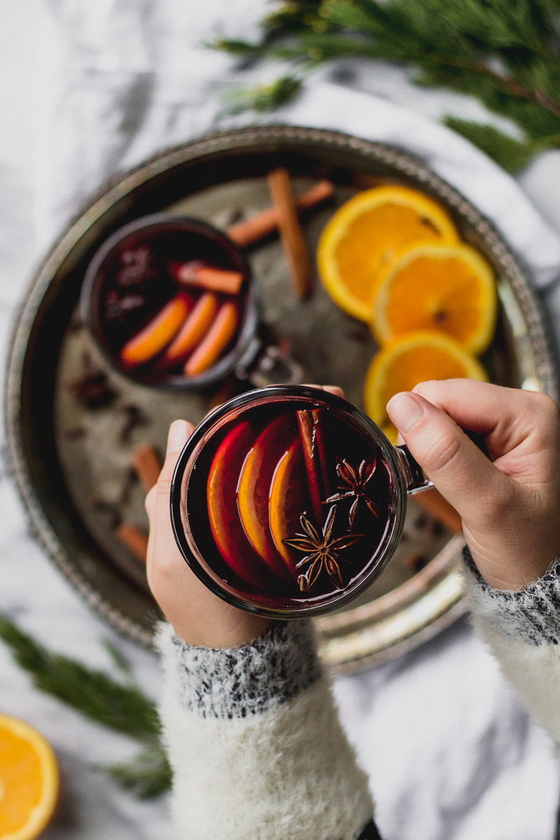 glass mug with mulled red wine, cinnamon, and orange slices on tray by fork in the kitchen