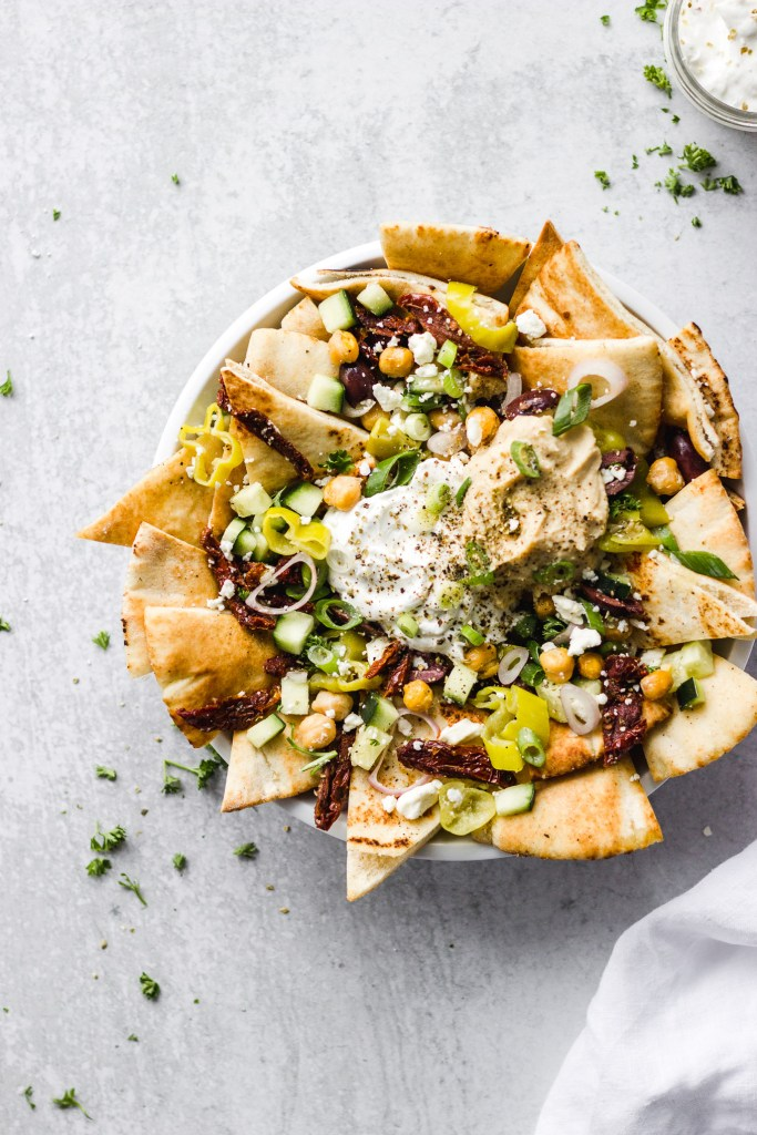 bowl of mediterranean nachos with dip by fork in the kitchen