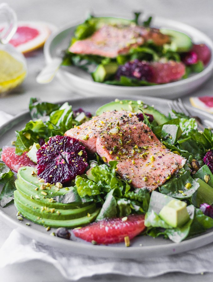 salmon citrus salad with avocado on plate by fork in the kitchen