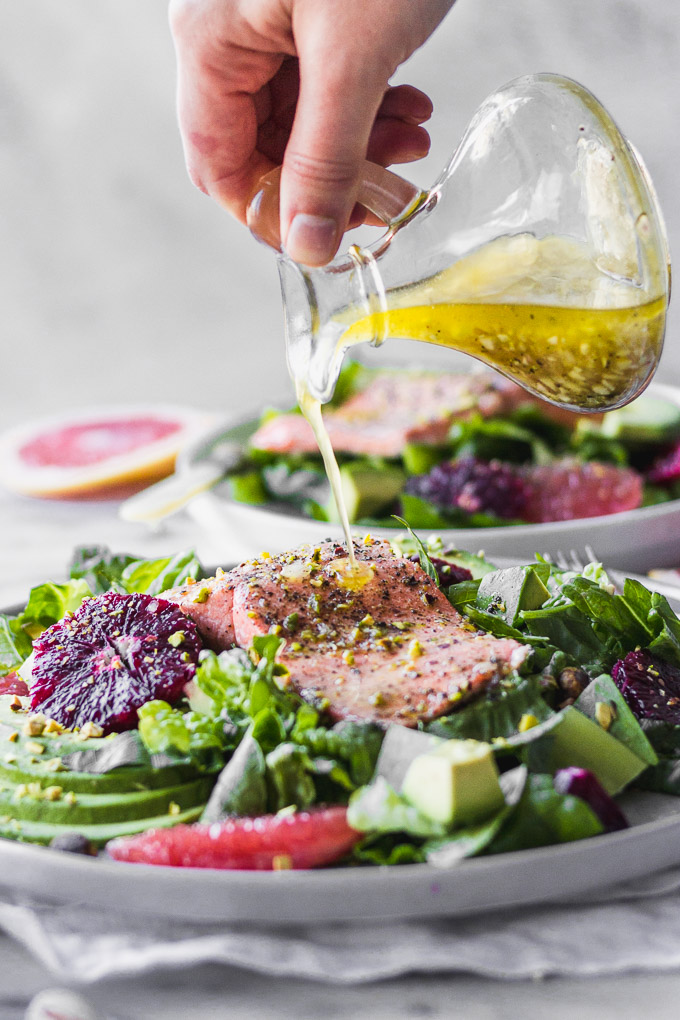 pouring dressing on salmon citrus salad with avocado on plate by fork in the kitchen