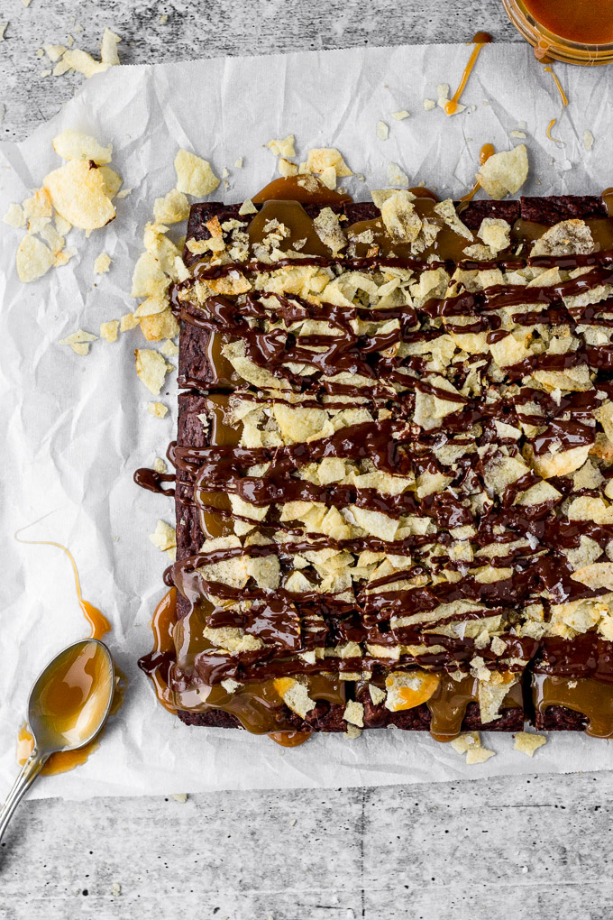 brownies with salted caramel, potato chips, and a chocolate drizzle by fork in the kitchen