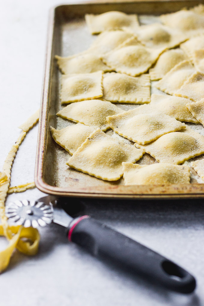 tray with homemade ravioli pockets uncooked next to pasta cutter