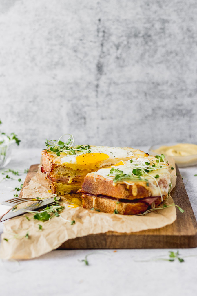 croque madame sandwiches with fried egg on board by fork in the kitchen