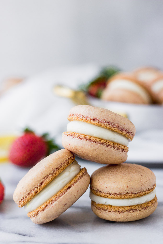 strawberry macarons stacked on marble board