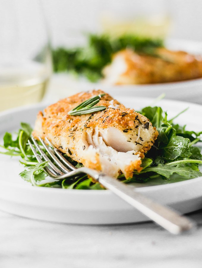 parmesan rosemary crusted cod on arugula with fork