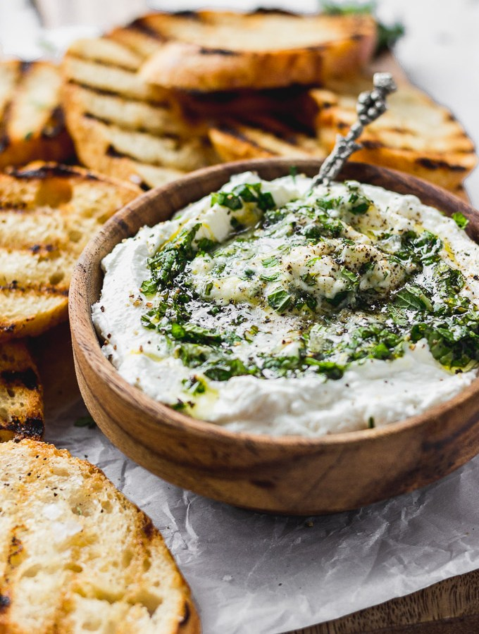 whipped ricotta with herbs and honey in wood bowl with grilled baguette