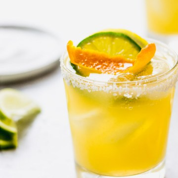 three citrus margaritas with salted rims and orange garnish