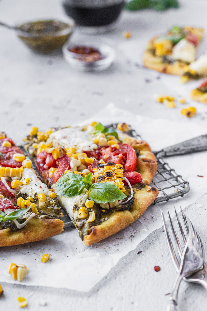 naan flatbread with burrata corn tomatoes and pesto on wire rack