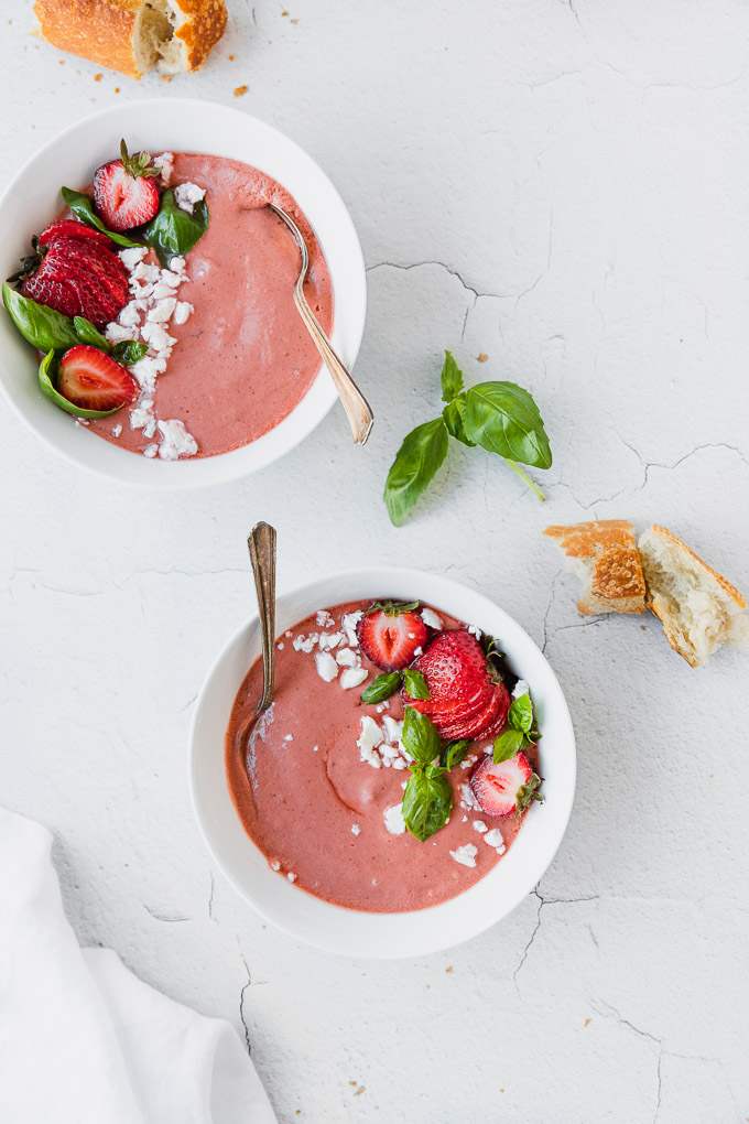two white bowls with pink strawberry basil gazpacho next to baguette and white linen