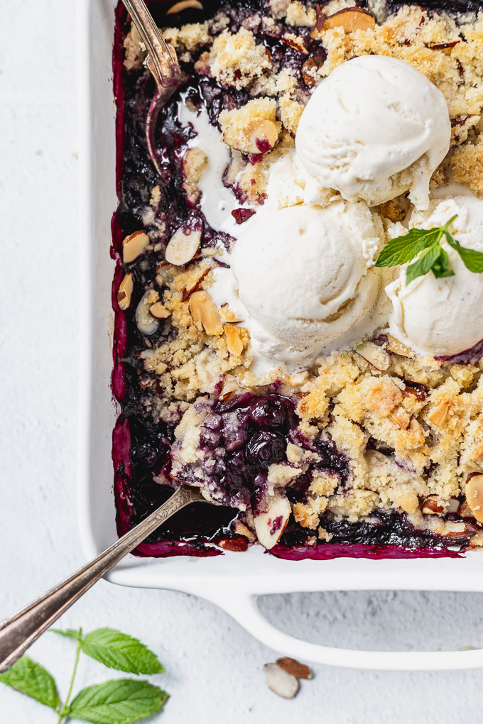 blueberry almond crisp with vanilla ice cream in a white baker and spoons