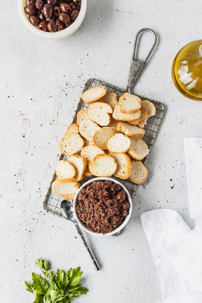 black olive tapenade with baguette crisps on tray
