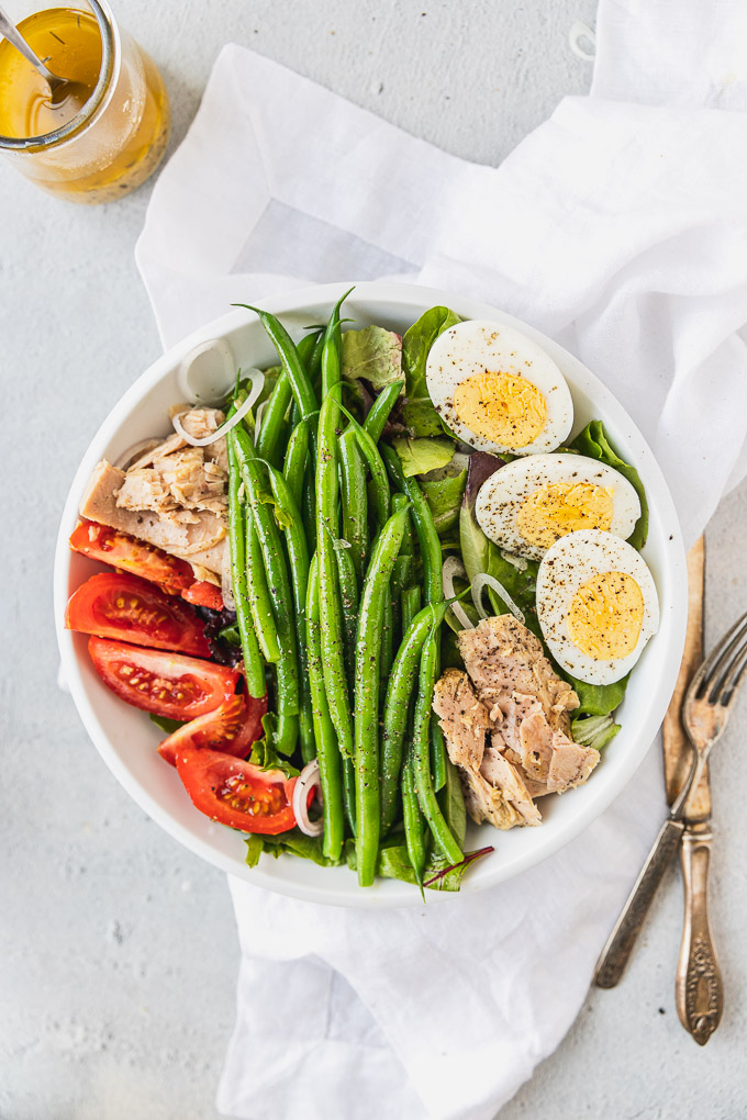 bowl with nicoise salad next to forks and knife and dressing