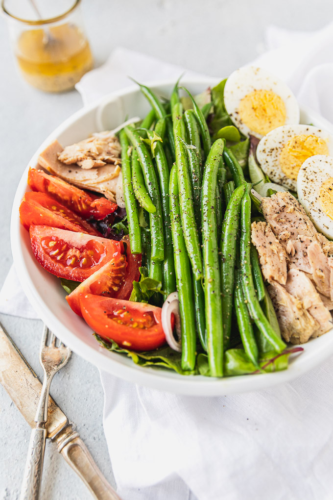 side view of white bowl with tuna and green bean salad