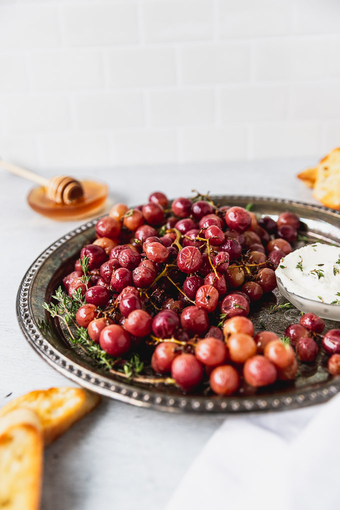 roasted grapes on platter with goat cheese and honey