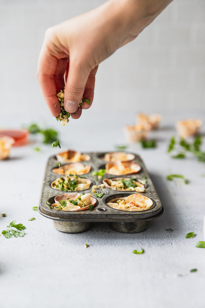 sprinkling cilantro on top of muffin tin with appetizer bites