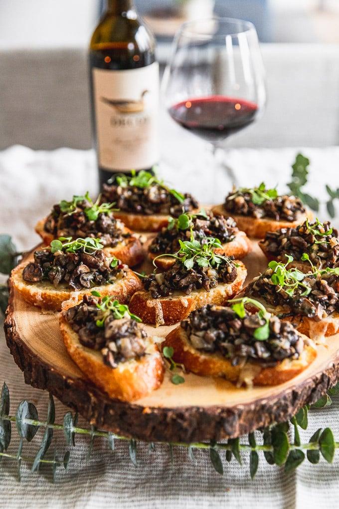 wooden serving plate with mushroom bruschetta next to wine