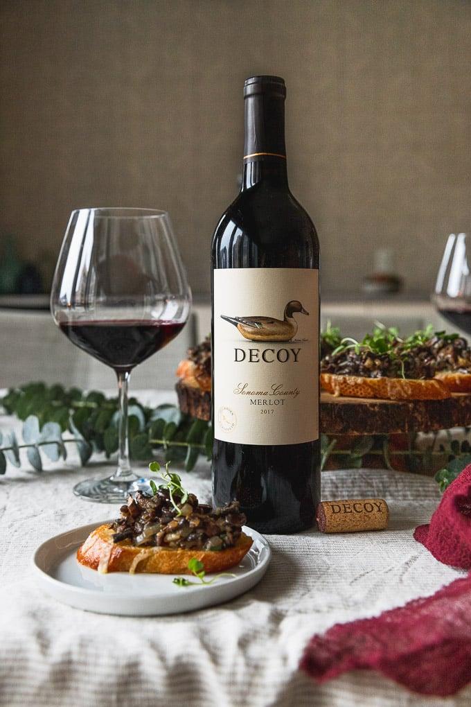 wine bottle next to glass and plate of mushroom bruschetta