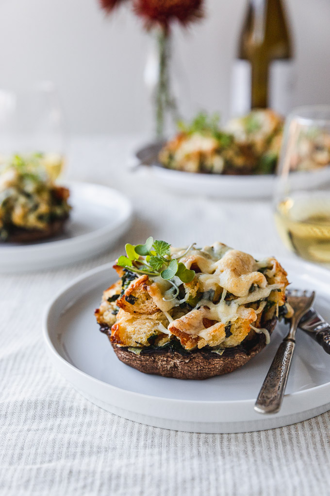 stuffed mushroom on a white plate with fork and knife on table next to wine with flowers in the background