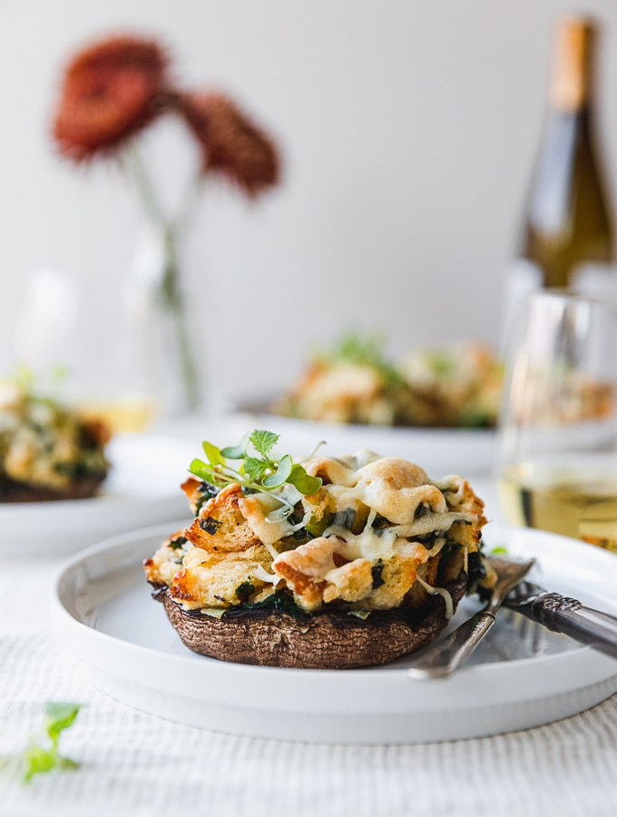 stuffed mushroom on a white plate with fork and knife on table next to wine