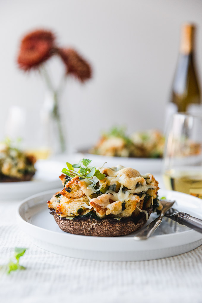 vegetarian stuffed mushroom on a white plate with fork and knife on table next to wine