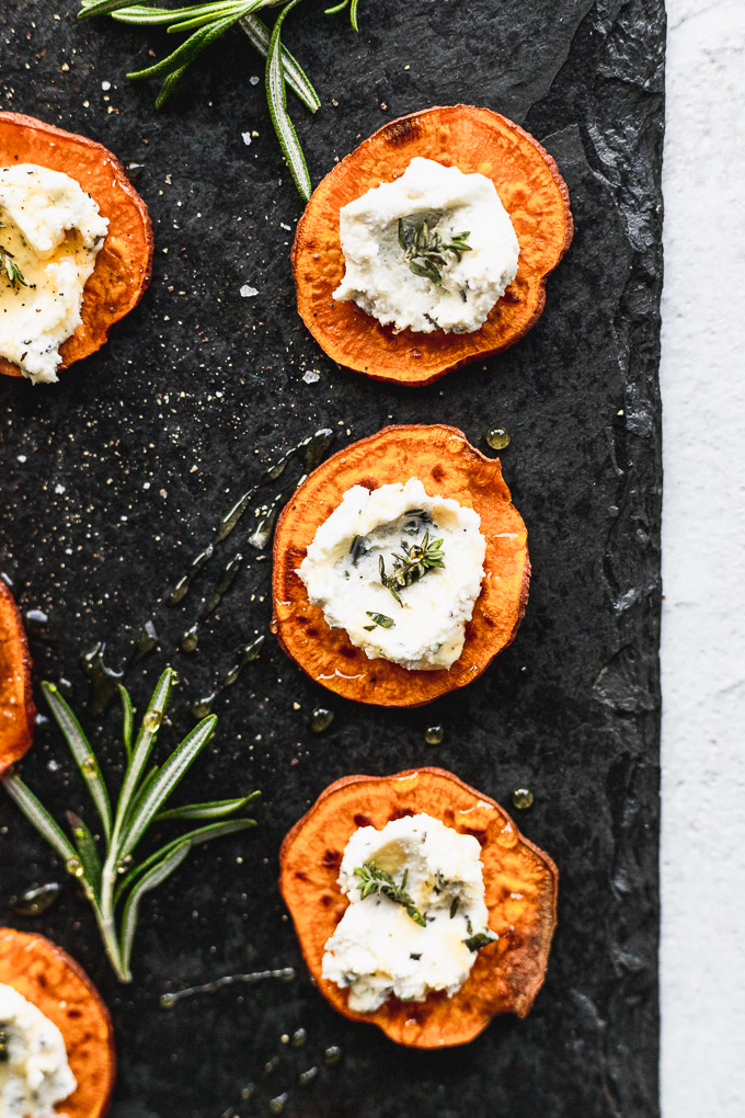 sweet potato goat cheese bites on black serving tray next to rosemary sprig