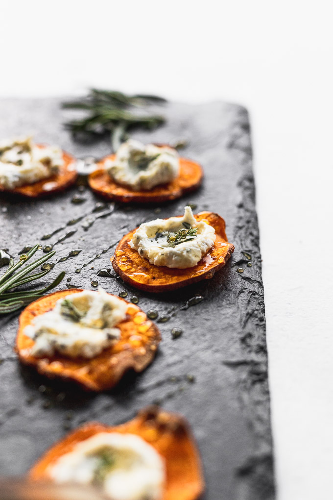 sweet potato with goat cheese on top of black serving tray from side