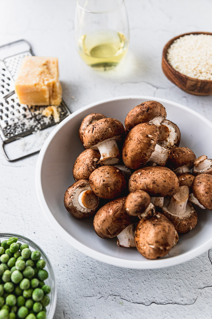 bowl of mushrooms next to peas with parmesan, wine, and arborio rice