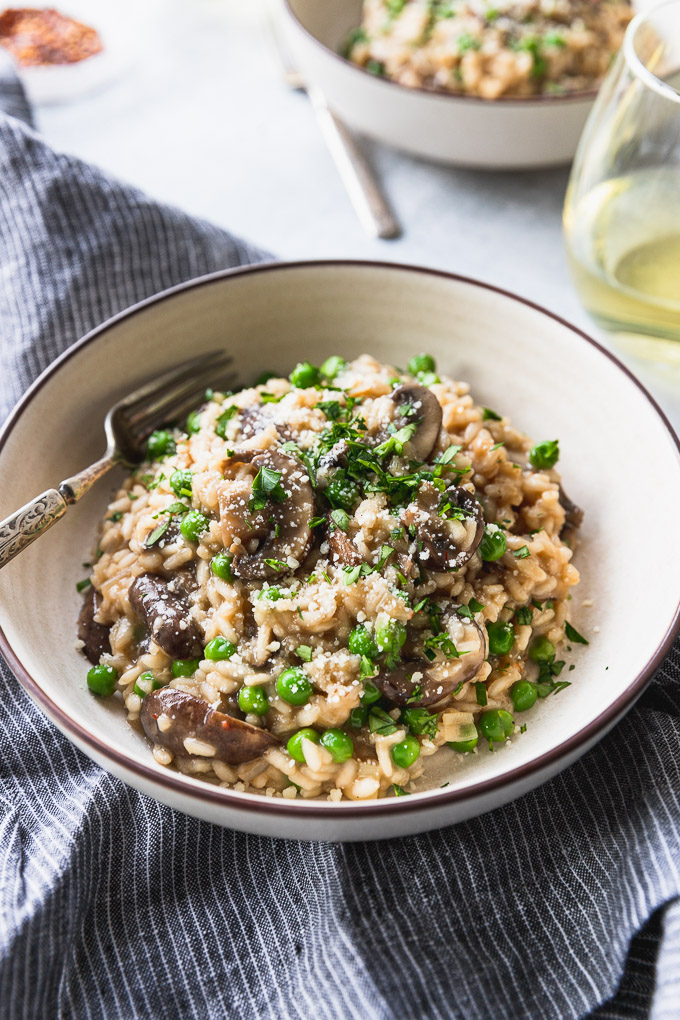up close look into bowl of mushroom pea risotto with fork next to it on top of a blue striped linen