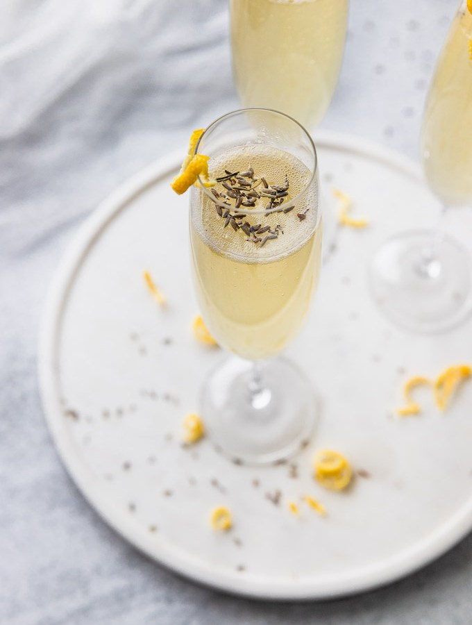 champagne flute with lavender flowers and french 75 with lemon twist