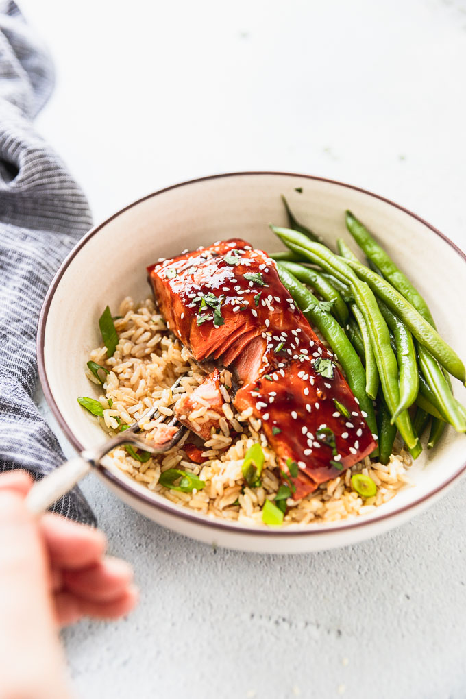 hand with fork taking a bite of teriyaki salmon in bowl