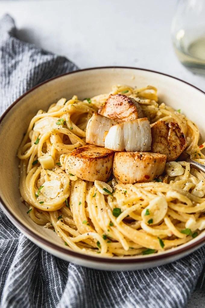 scallop cut open on bowl of creamy garlic pasta