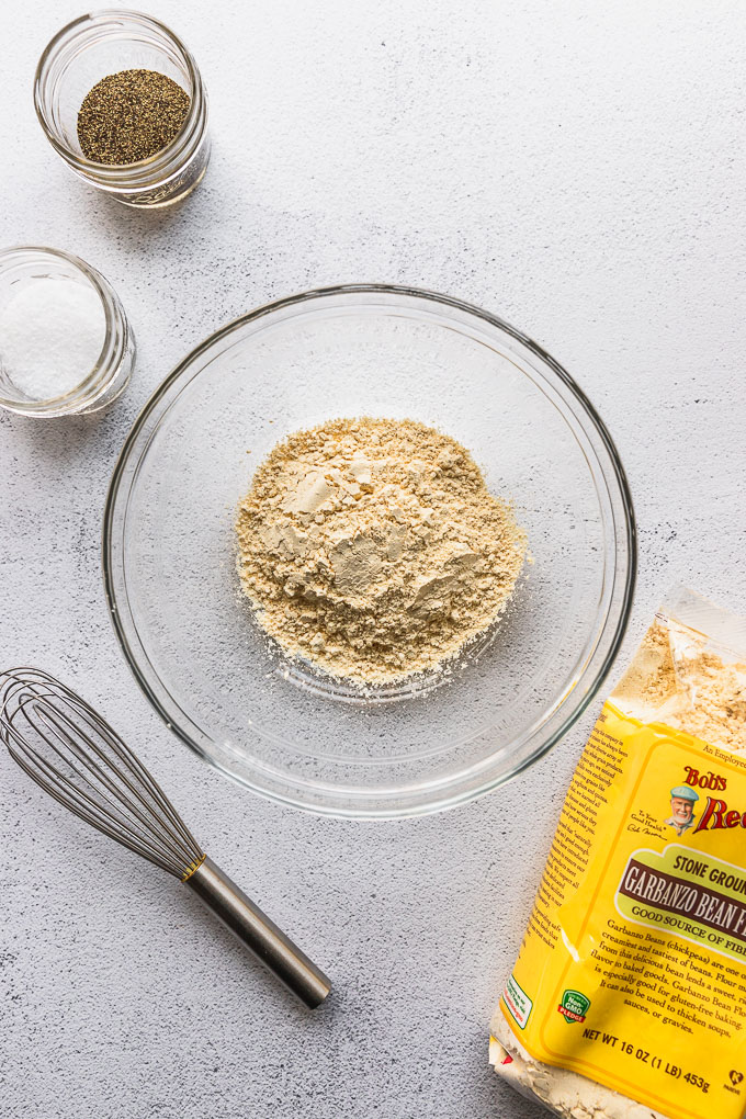 chickpea flour in bowl next to whisk, salt, and pepper