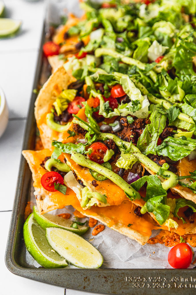 up close view of nachos on sheet pan with avocado sauce, tomatoes, and lettuce