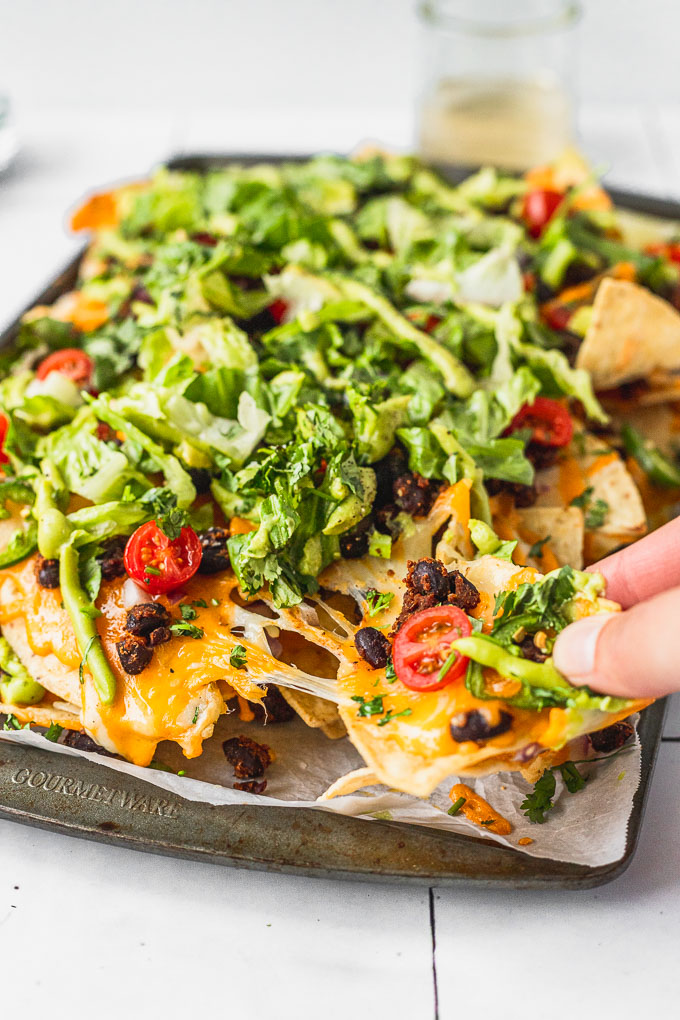hand pulling nacho with cheese pull