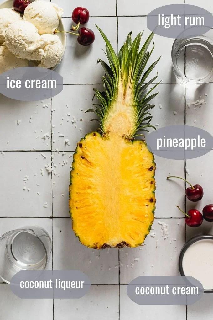 flat lay with pineapple sliced open, ice cream, liquor, cherries, and coconut cream