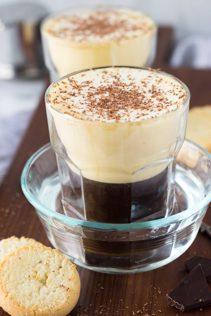 glass of egg coffee with chocolate shavings sitting in a ramekin of water on a wood tray