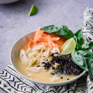 A thai-style soup with chicken and forbidden black rice with basil on a blue table.