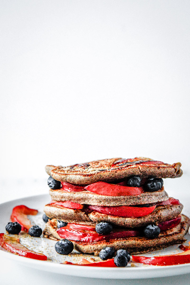 Pluot brown sugar buckwheat pancakes stacked on a white plate on a white table.