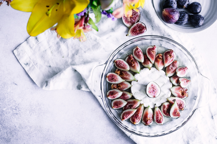 A baking dish with brie and figs with yellow flowers.