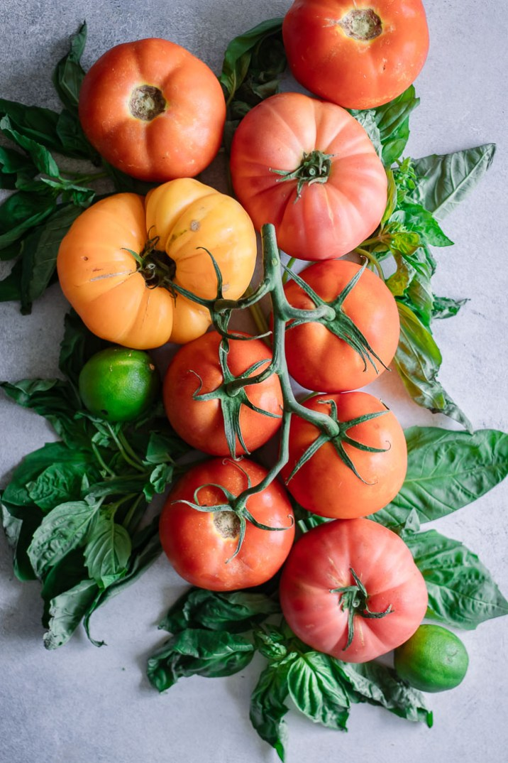An arrangement of fresh tomatoes with basil on a white table.