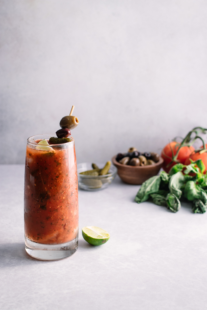 A bloody mary in a tall glass with olives, basil, pickles, and tomatoes.