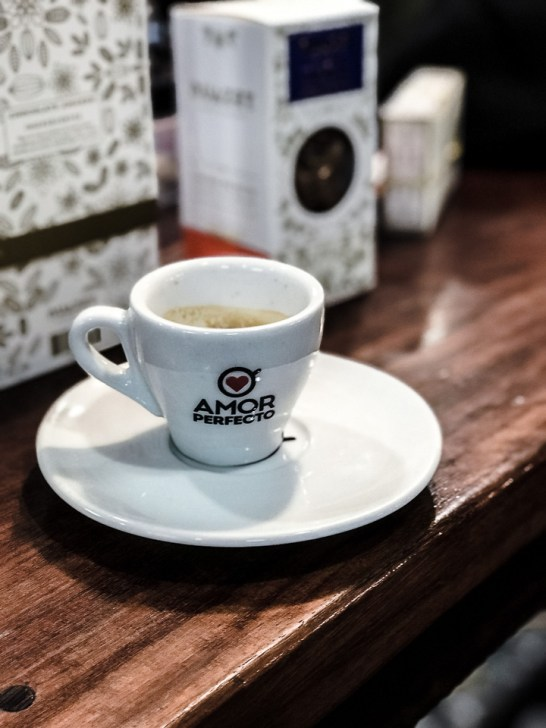 A white espresso cup in a white saucer on a wood table in a coffee shop.