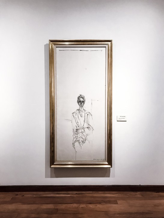 A white painting of a nude woman on a wall in an art gallery.