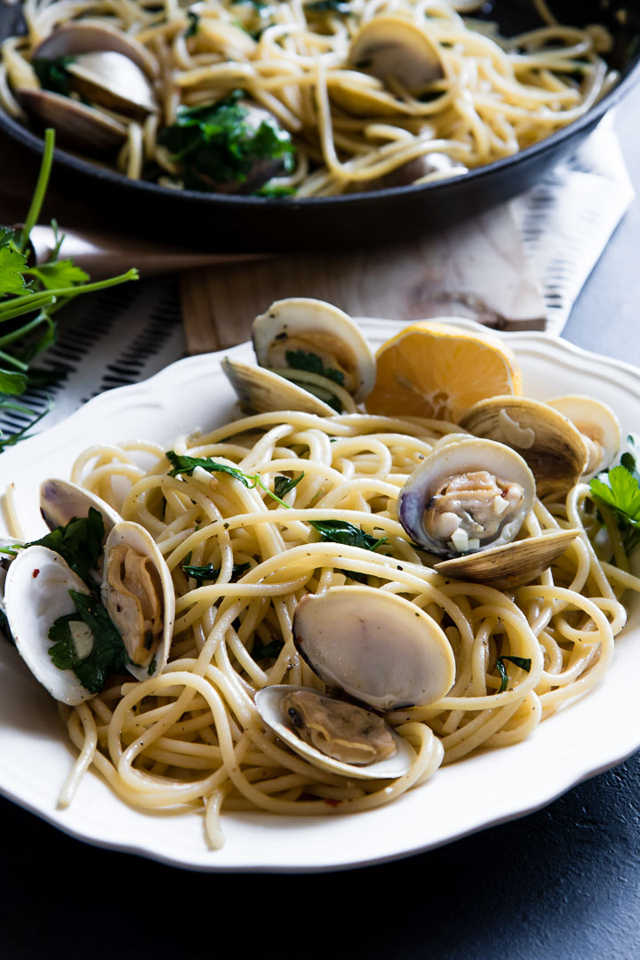 Pasta with clams in a white plate on a black table.