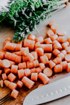 Diced carrots on a cutting board with a knife and parsley in the background.