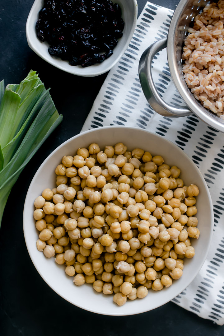 A bowl of chickpeas on a black table with a colander of farro and a leek on the side.
